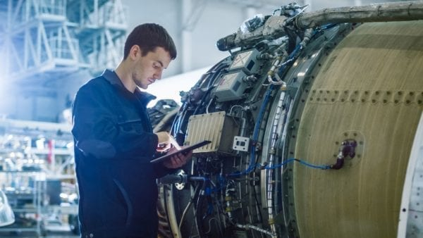 Aircraft Maintenance Mechanic Inspecting and Working on Airplane Jet Engine in Hangar