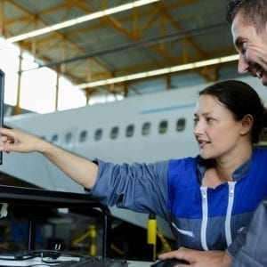 female aircraft mechanic pointing at laptop